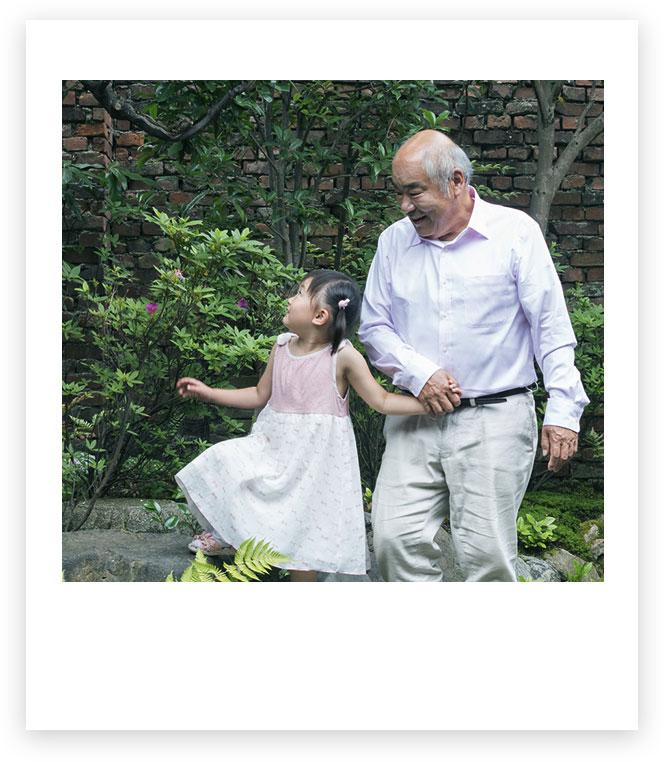 Avô e neta de mãos dadas ao ar livre