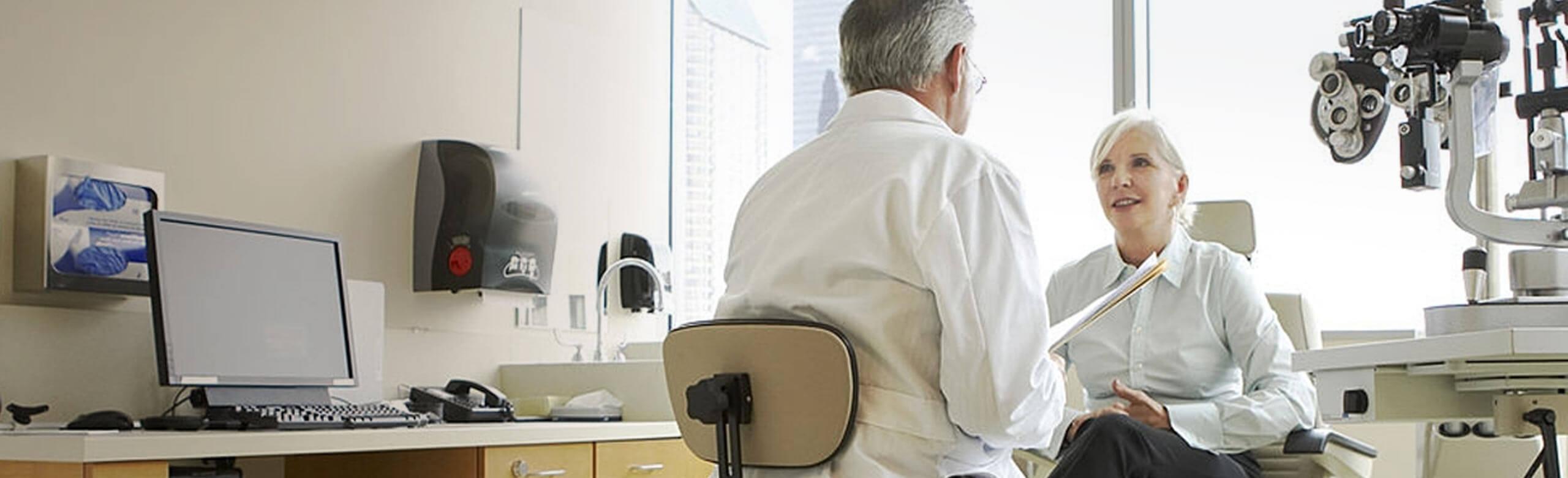 Oftalmologista e paciente conversando na sala de exames