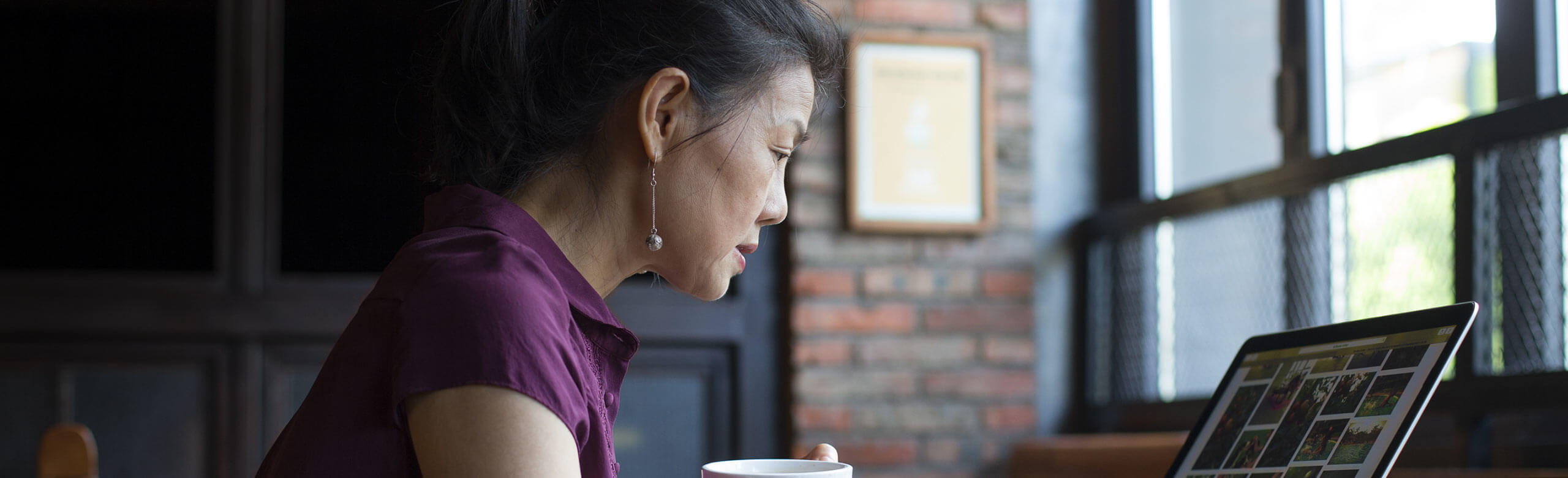 Mulher bebendo café e trabalhando no notebook