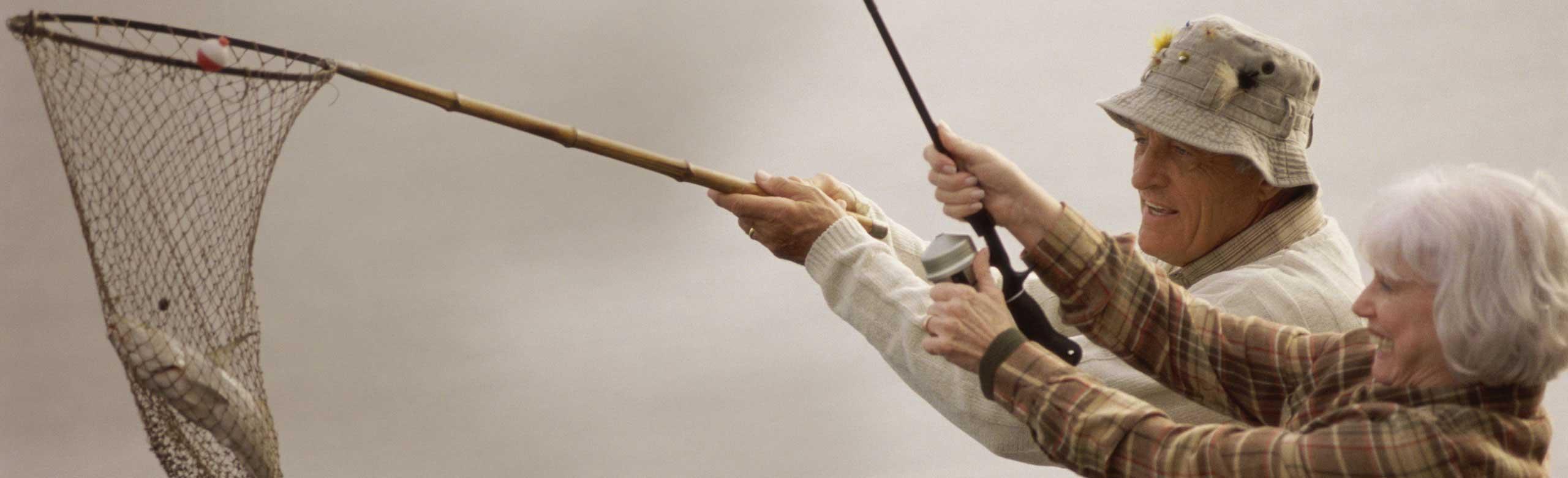 Casal de idosos pescando com uma rede e uma vara de pesca