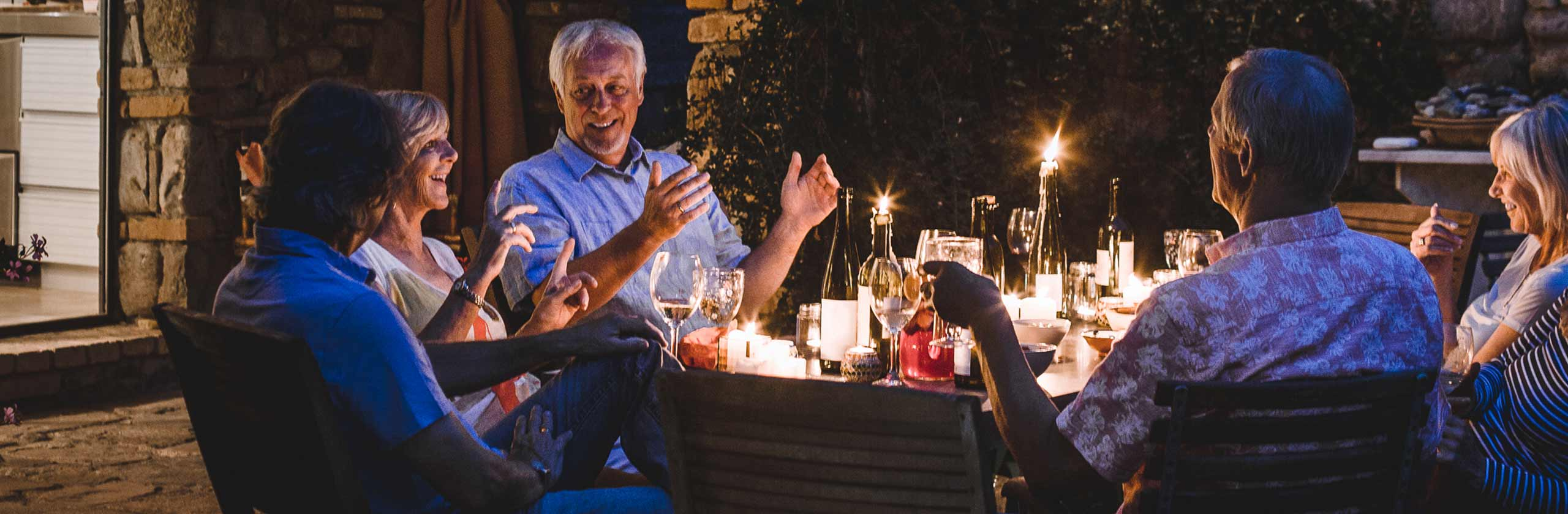 Pessoas reunidas ao redor de uma mesa de jantar ao ar livre