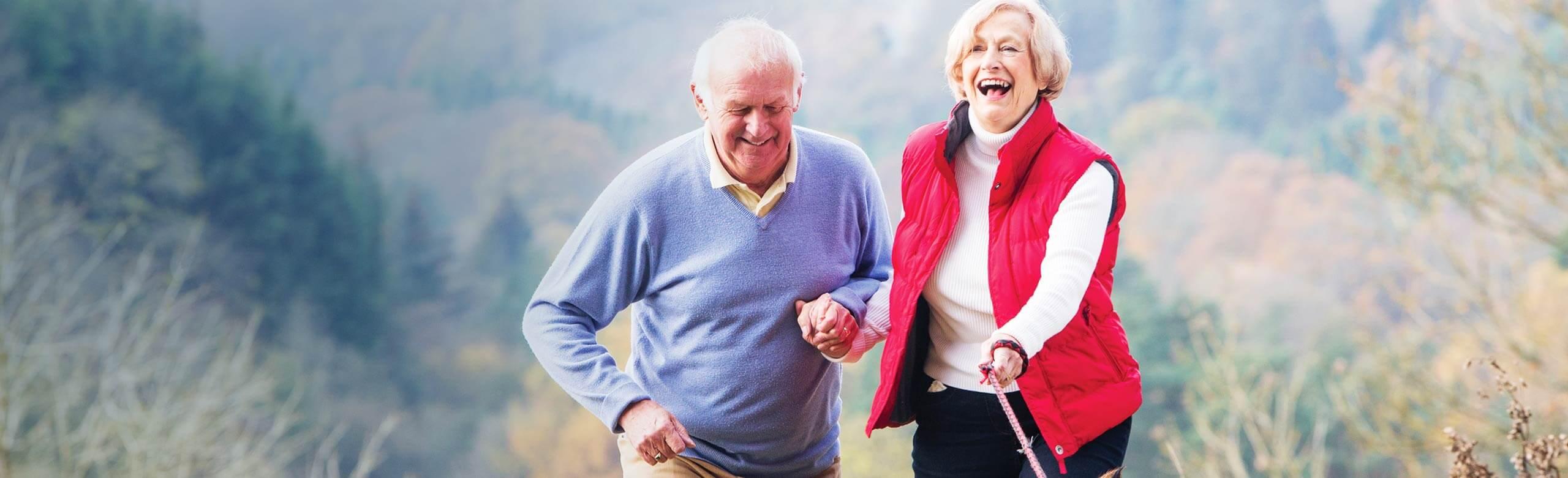 Homem e mulher de mãos dadas andando ao ar livre e rindo