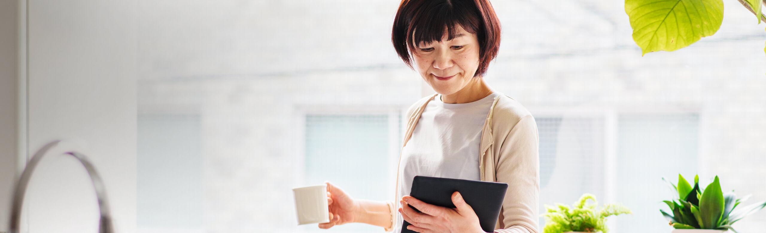 Mulher segurando uma caneca e um tablet