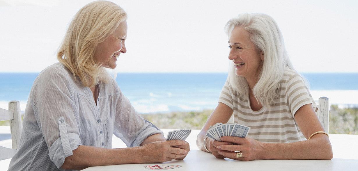Duas mulheres jogando cartas perto do mar